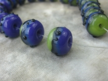 violet green lampwork bead string closeup